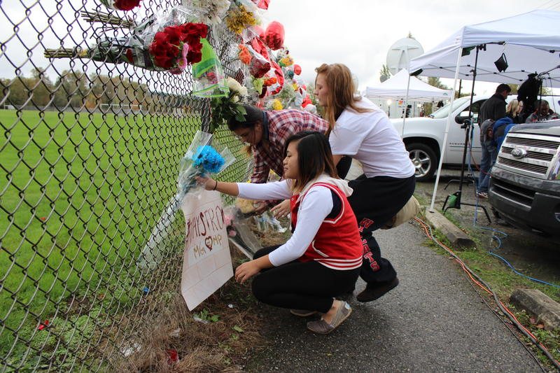 Students put flowers on a memorial for the shooting victims at Marysville-Pilchuck High School in October 2014.