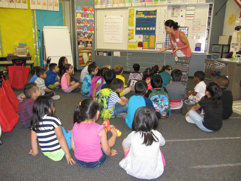 Teacher Natalie Alonzo welcomes kindergarten students to the first day of the Jump Start program at Hazel Valley Elementary School in Burien.