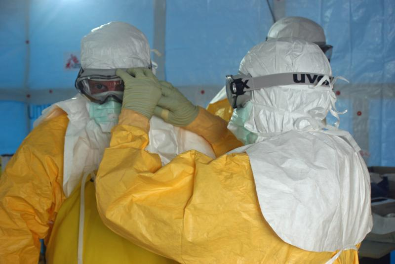 A Doctors Without Borders staff member ties the face mask of Dr. Jordan Tappero, CDC, before Dr. Tappero enters an Ebola treatment unit in Liberia.