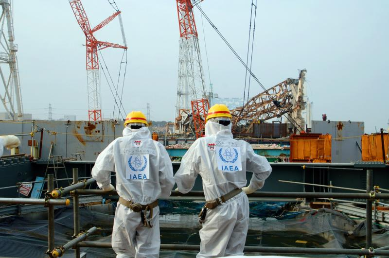 Two IAEA experts examine recovery work on top of the Fukushima Daiichi Nuclear Power Station in April 2013.