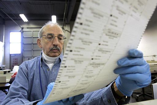 Election worker Ed Faccone looks over a ballot to see why it would not read in a tabulating machine at a King County election tabulating center Wednesday morning, Nov. 17, 2004, in Seattle.