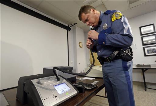 Wash. State Trooper Mel Sterkel demonstrates the patrol's newest breath testing instrument, used to measure alcohol levels in drivers suspected of drunken driving, Nov. 5, 2014, in Seattle.