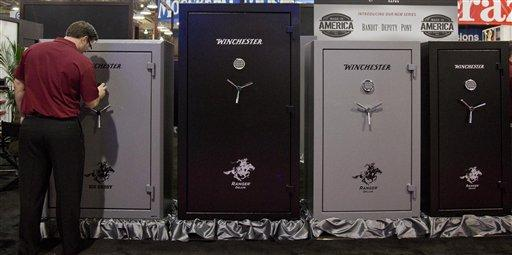 A Winchester Safes representative sets the lock on one of several gun safes on display at the 35th annual SHOT Show, Tuesday, Jan. 15, 2013, in Las Vegas.