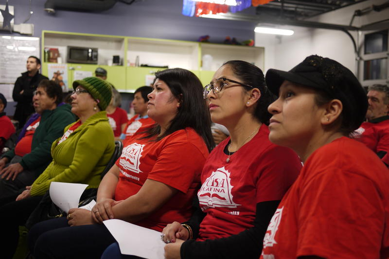 Women at Casa Latina watch the president's speech.