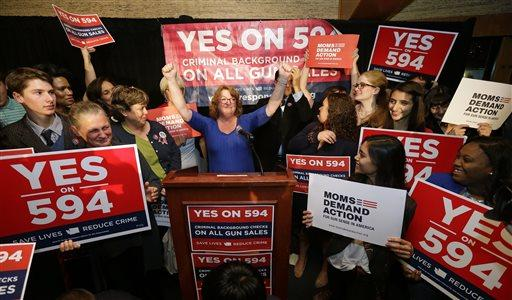 Cheryl Stumbo, center, raises her arms as she finishes speaking at an election night party for Initiative 594, a measure seeking universal background checks on gun sales and transfers, Tuesday, Nov. 4, 2014, in Seattle.