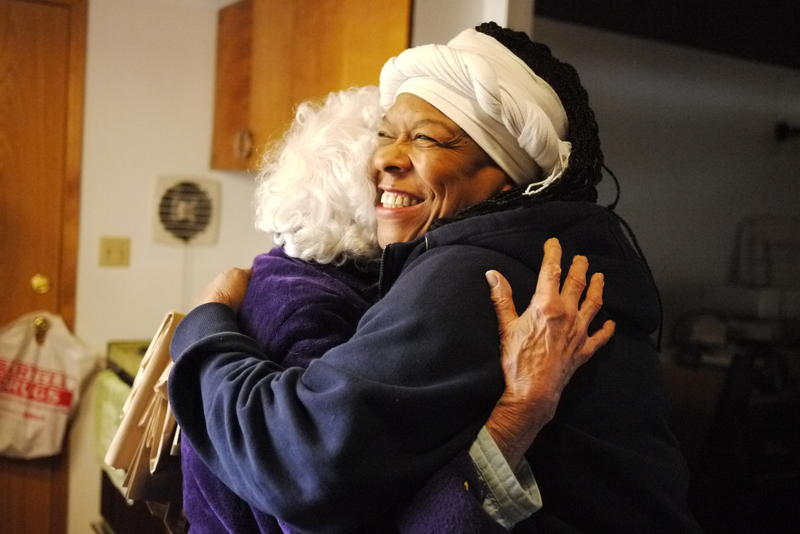 Fai Mathews, a driver for Meals on Wheels, hugs a client at her home in North Seattle.