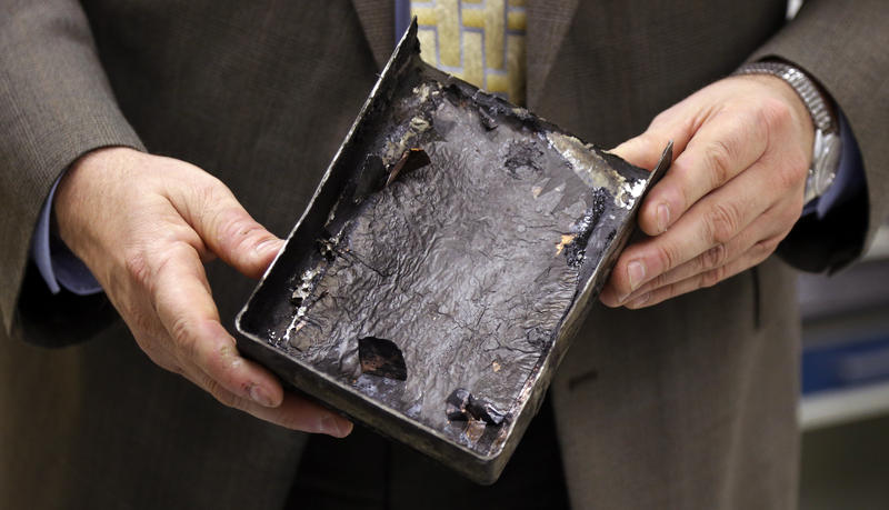 NTSB's Joseph Kolly, holds an fire-damaged battery casing from the Japan Airlines Boeing 787 Dreamliner that caught fire at Boston's Logan Airport, at the NTSB laboratory in Washington, D.C., Jan. 24, 2013.