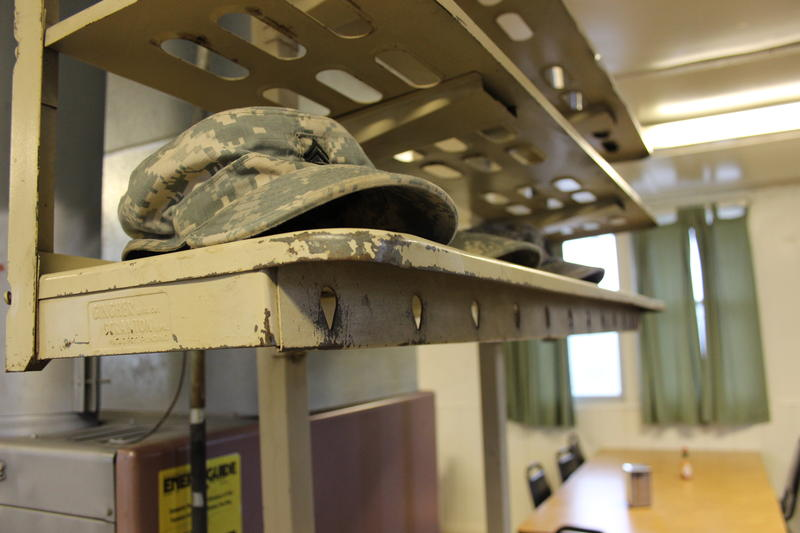 Soldiers place their hats on rack just inside the mess hall doors before eating breakfast in the controlled monitoring area at JBLM.