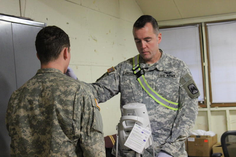 Maj. Dr. Eric Jacobson checks the temperature of a soldier in the controlled monitoring area of Joint Base Lewis-McChord on the morning of Jan. 13, 2015. It was day 13 of the 21 day Ebola monitoring period for the cohort that returned from Liberia.