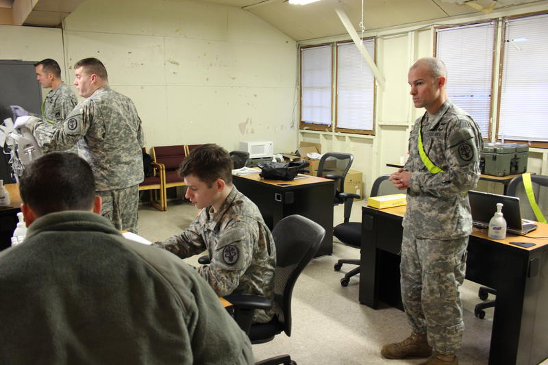 (left to right) Maj. Dr. Eric Jacobson and Staff Sgt. John Miles take temperatures of soldiers in the controlled monitoring area for Spc. Christopher Appleseth to record as Lt. Col. Dr. Rodd Marcum looks on.