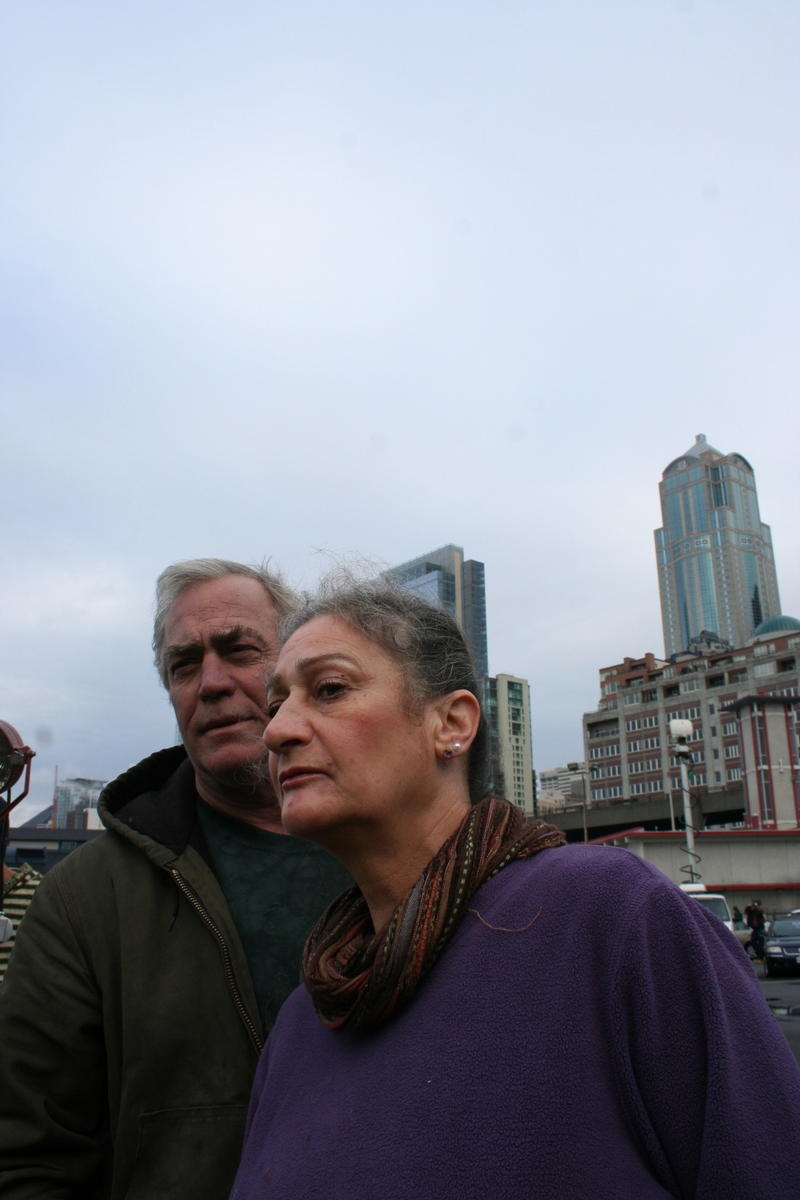 Carl Sheats and Kathy Barth of Brinnon, Washington, look at the dead gray whale as they wait for the ferry.