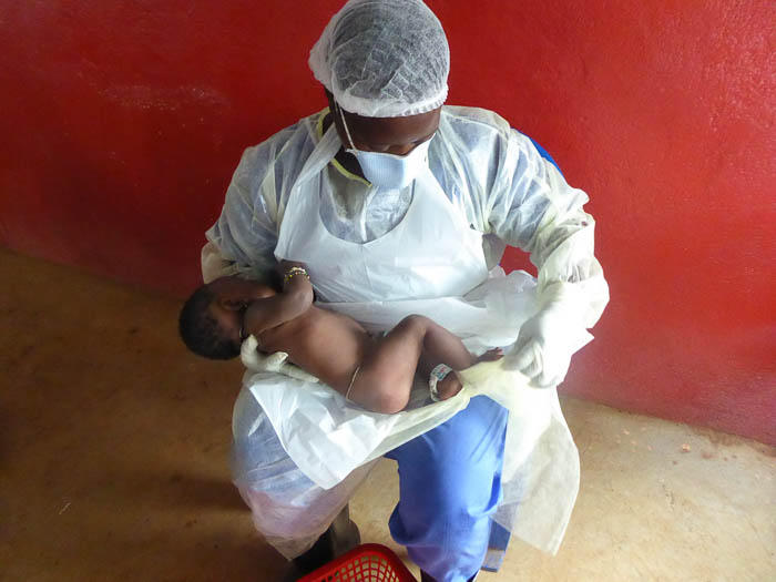 A health care worker gives some much needed maternal care to an infant whose mother died from Ebola.
