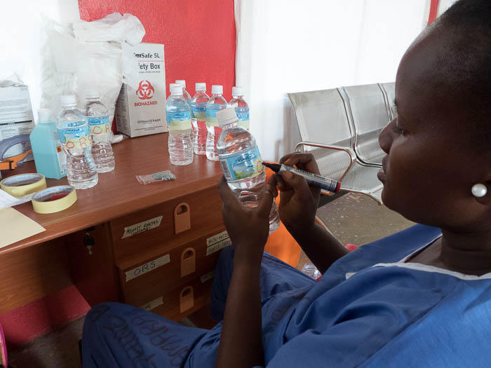 A health worker makes oral rehydration solution -- one of the basic treatments for Ebola. Patients lose up to 5-10 liters of fluids every day which need to be replaced.