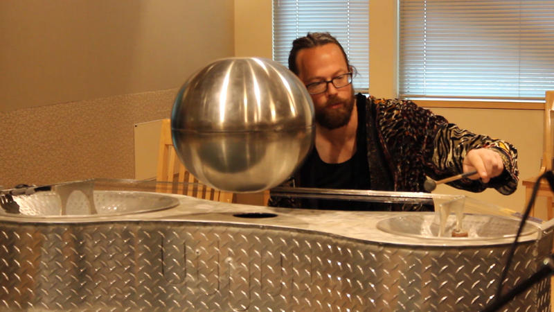 "Lelavision co-founder Ela Lamblin performs on the ""metalphor,"" a large instrument he designed and built himself. It looks futuristic, but sounds similar to a sitar."