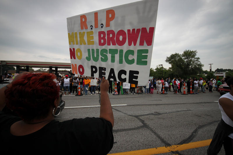 "A protester of the shooting of Michael Brown in Ferguson, Missouri, holds up a sign reading ""No justice, no peace"" -- a popular slogan."