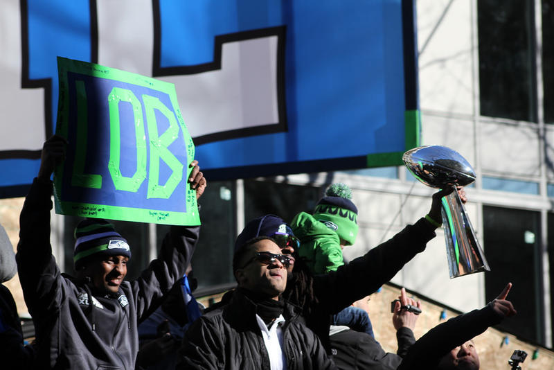 "Seahawks Legion of Boom members Jeremy Lane, Earl Thomas and Richard Sherman show off the trophy at the Super Bowl parade last January. The organization wans to trademark ""boom"" and the number 12."