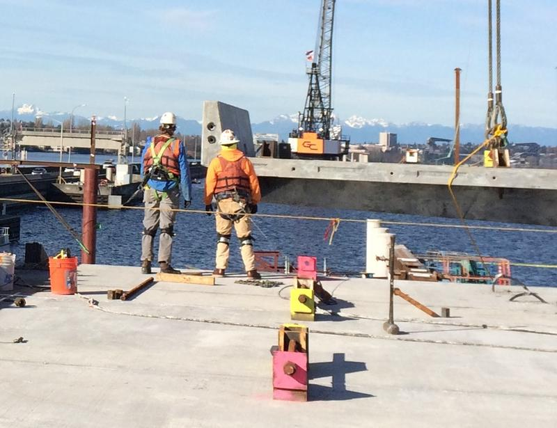 Workers prepare to snap in a new section of roadway on the east side of the SR 520 bridge.