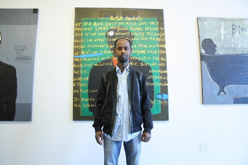 Admassu Addisu stands in front of a painting by Ethiopian Artist Emanuel Tegene, on display in the Tobya Art Gallery. It's part of an artists' loft building intended to spur pedestrian-oriented development around Mt. Baker Station.