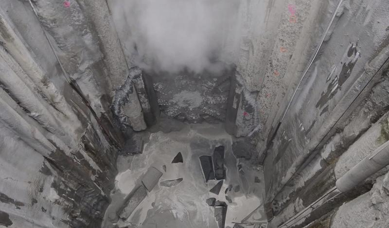 Bertha, the tunnel boring machine, emerges from more than a year of captivity. The machine's turbines can be seen beneath the plume of dust.