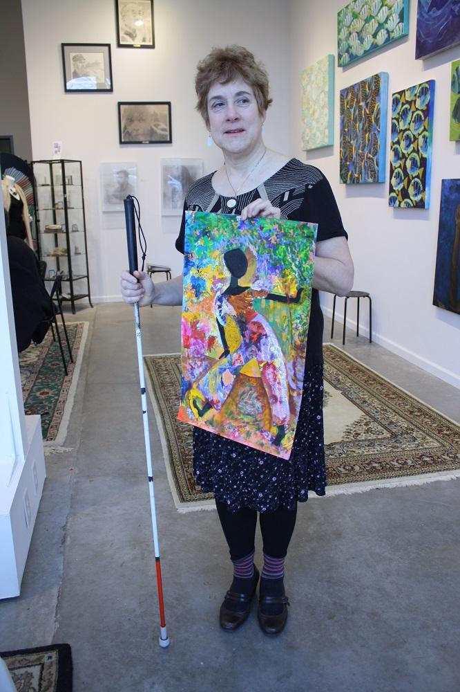 Barbara Oswald holds up one of her paintings at the gallery she runs at Mt Baker Lofts. Oswald says being blind, she might not capture what a subject looks like, but