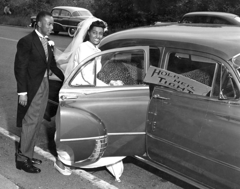 A newlywed bride and groom from 1955. Rashida Robinson reports these are her grandparents, Howard Rhone and Deloris Berry Rhone. Robinson writes: I just spoke with my grandmother and she remembered every detail about this photo, down to the leopard seats
