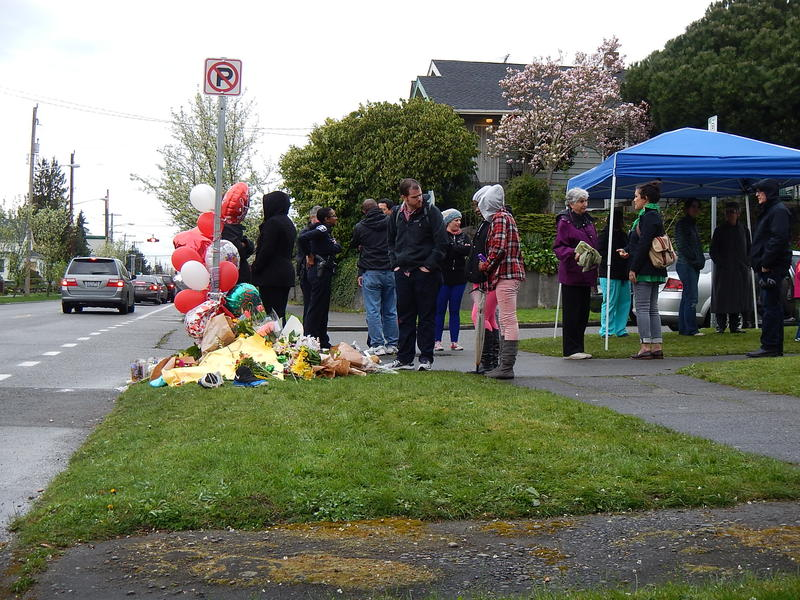 Mourners gather at the South Seattle street corner where Robert Robinson, Jr., was killed in a drive-by shooting on Sunday.