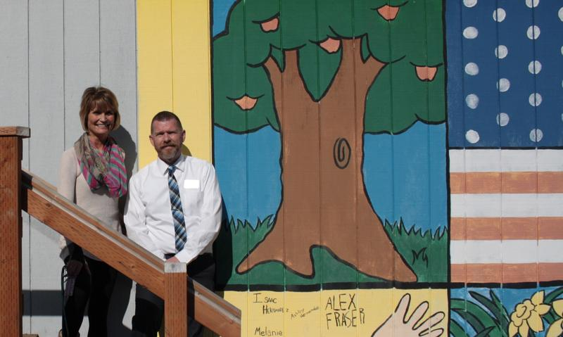 In Puyallup, one of many portable classrooms used to relieve school overcrowding. The portable is decorated with a mural painted by kids: it shows an apple tree, a hand and an American flag.