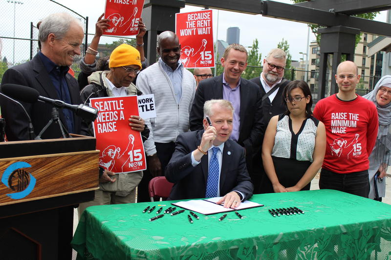 A day after it received final approval in City Council, Seattle Mayor Ed Murray signs the new $15 an hour minimum wage law