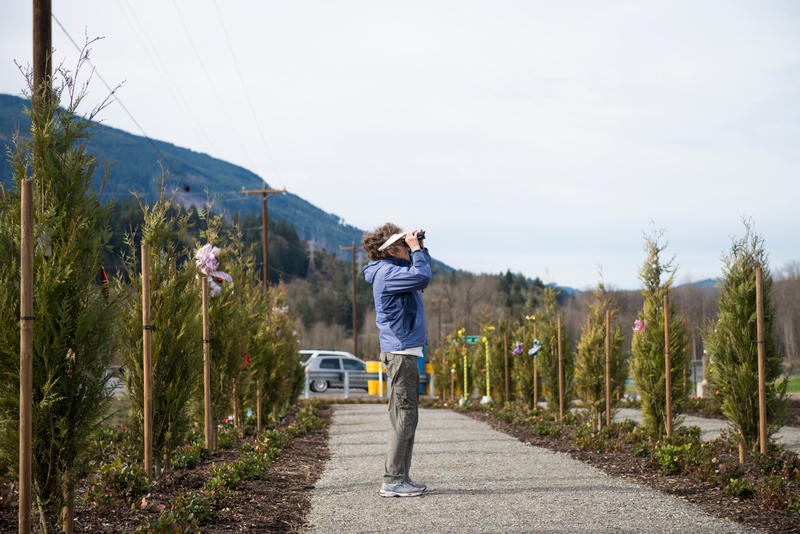 Christine Brown takes a photograph near the entrance to the former Steelhead Haven in Oso, Wash.