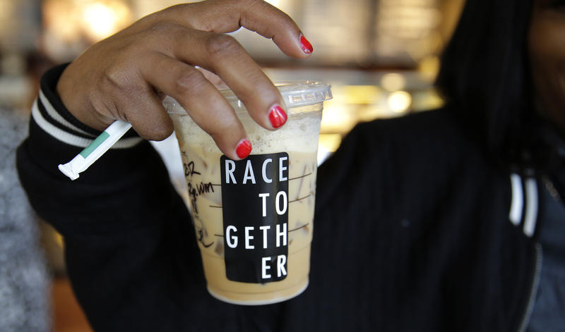 "Larenda Myres holds an iced coffee drink with a ""Race Together"" sticker on it at a Starbucks store in Seattle, Wednesday, March 18, 2015."
