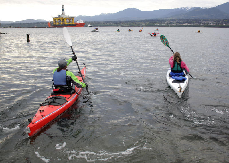 Kayakers slide into the water as the Polar Pioneer approaches its anchorage in Port Angeles aboard the Blue Marlin on Friday.