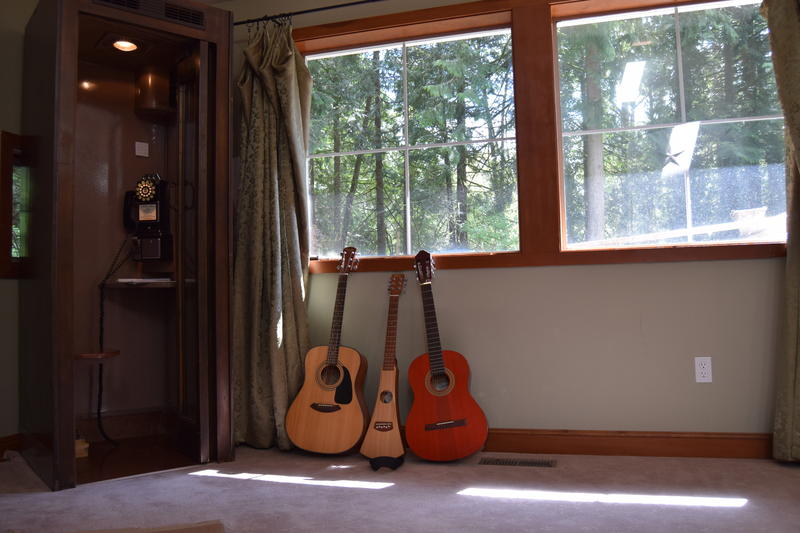 The front room of the main house at reSTART, an inpatient digital recovery treatment facility, has guitars leaning against a rotary phone, which clients can use to call out.