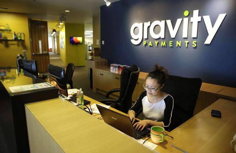 Cary Chin works Wed. at the front desk of Seattle-based Gravity Payments. CEO Dan Price told his employees this week that he was cutting his own salary and using company profits so they would each earn a base salary of $70,000.