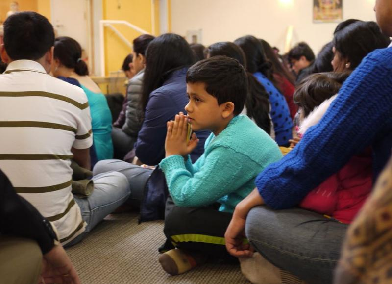 Akshar Koirala, 7, of Renton, prays with the Nepali community in Bothell following the 7.8-magnitude earthquake.