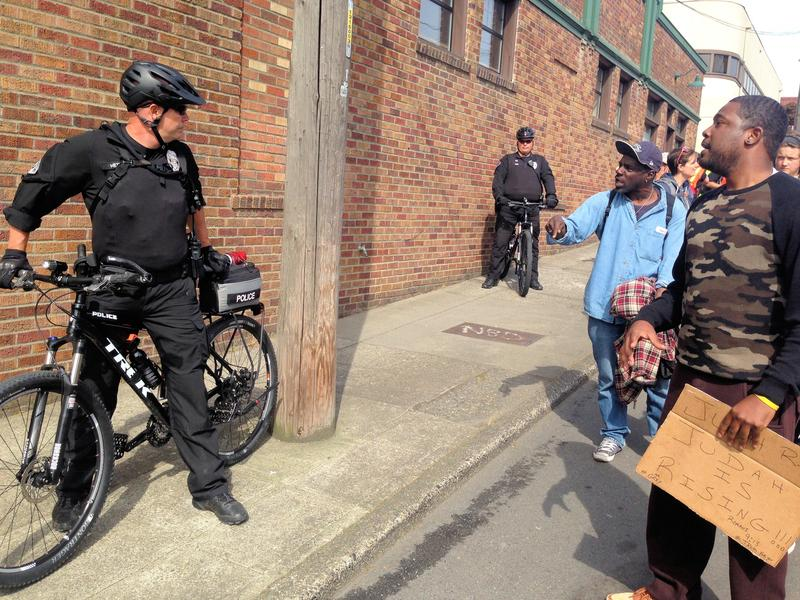 People vent to police officers along the May Day march route in Seattle on Friday.
