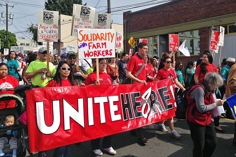 People walk in the May Day labor march in Seattle on Friday, May 1, 2015.