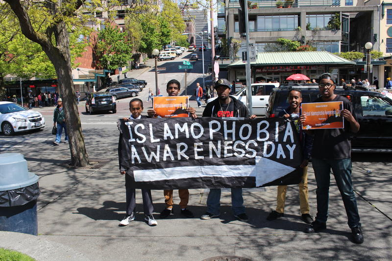Holding the sign pointing to Islamophobia Awareness Day