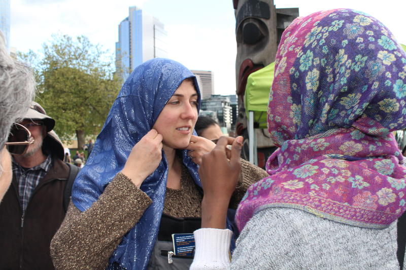 A passer-by tries on a hijab at Islamophobia Awareness Day