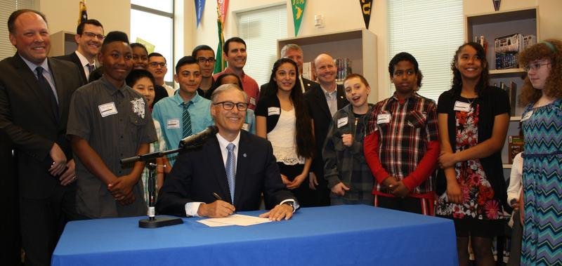 Gov. Jay Inslee signs a bill expanding the College Bound program. Behind him, middle schoolers from Mill Creek Middle School in Kent. At far left is Sen. David Frockt, who wrote the bill.