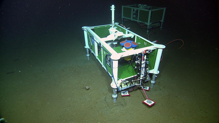 An Acousitic Doppler Current Profiler (four blue-red cyllinders with yellow housing) is installed at the base of Axial Seamount.
