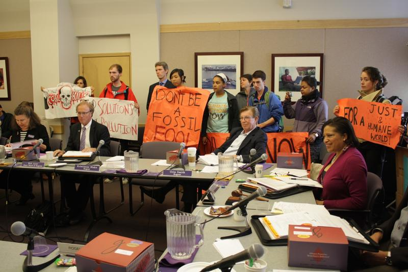 Protesters hold signs around a table populated by UW Regents.