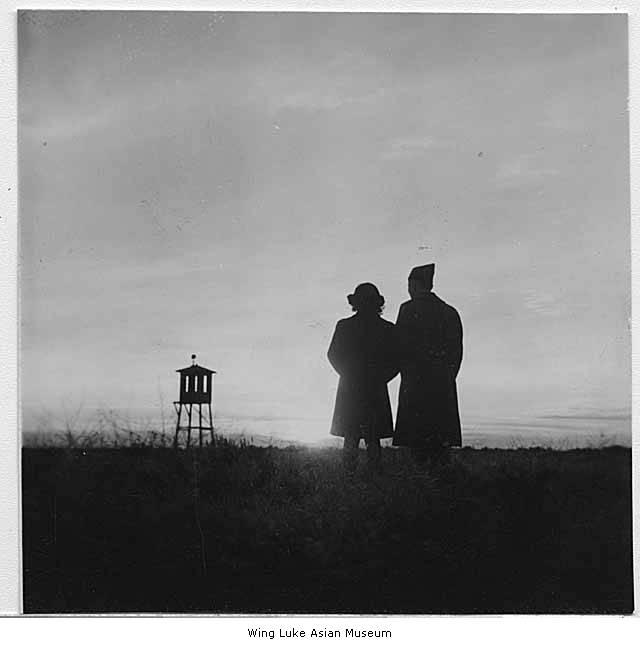 Woman and soldier watching sun set behind Minidoka watchtower in Idaho, 1944.