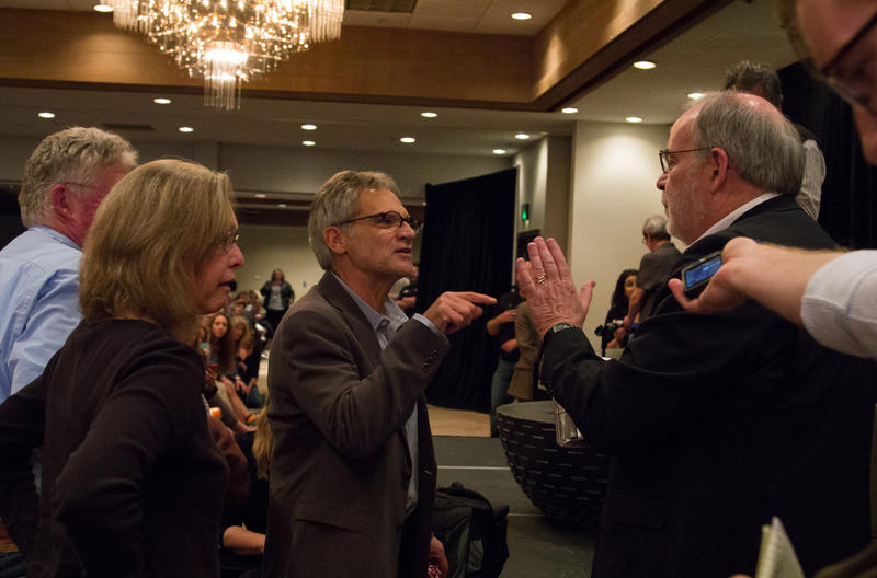A man who identified himself as Missoula attorney Thomas Dove, right, elbows his way to the stage at a forum open to the public on May 6, accusing author Jon Krakauer, center, of lying and using confidential documents in his new book about rape in Missoul