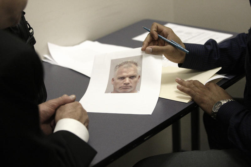 A Dallas police officer shows a robbery victim a photo of a suspect in 2009. The Dallas police department in Dallas has been a leader in blind lineups, which experts say reduces mistakes made by eye witnesses.