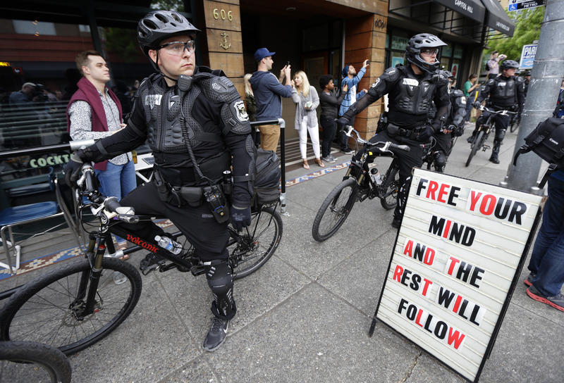 Police officers pause next to a sign outside a restaurant as they observe a May Day anti-capitalism march, Friday, May 1, 2015 in Seattle.
