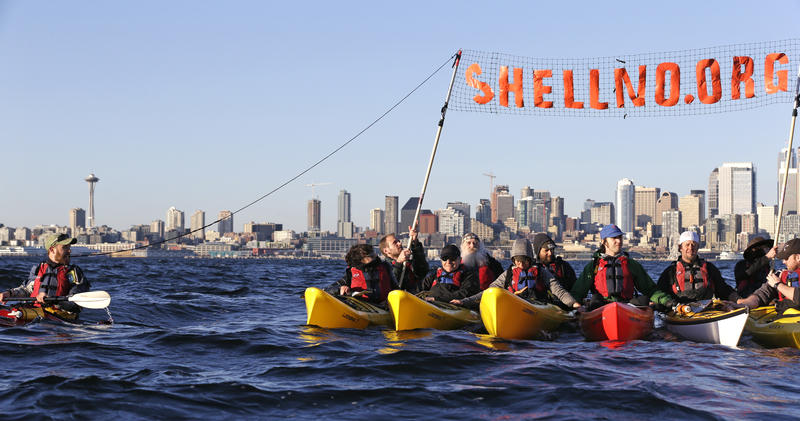 A group of kayakers rafted together work to pull up a protest sign as they practice for an upcoming demonstration against Arctic oil drilling, in Elliott Bay on April 16, 2015.