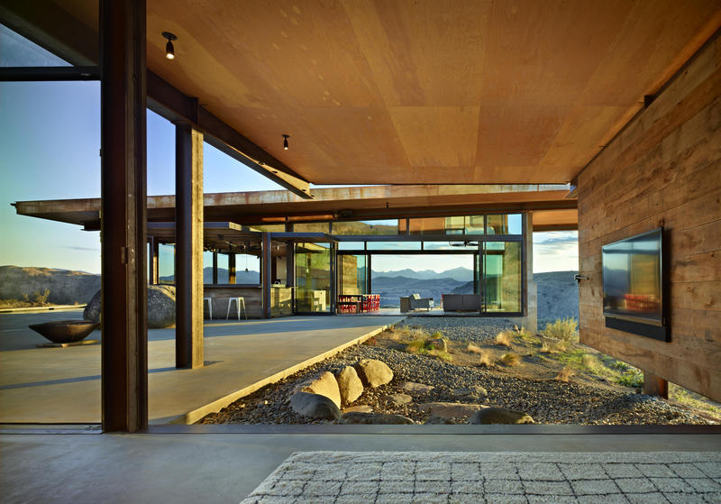 An entire wall of the Studhouse den opens to the courtyard. Living and dining spaces are seen in the adjacent pavilion. Studhorse