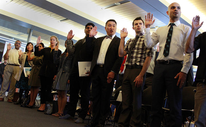 New American citizens take the oath at Seattle City Hall on Flag Day on Sunday.