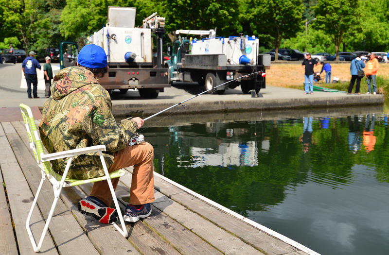 Anglers watch as workers from the Washington Department of Fish and Wildlife prepare to pour two truckloads of rainbow trout into Green Lake the Friday before Father's Day. These fish came from the state hatchery in Arlington.