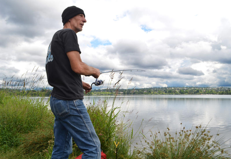 James Bragg of Seattle fishes as he watches state workers prepare to plant fish in Seattle's Green Lake on Friday, June 19. He says he's been fishing most days for the past four years.